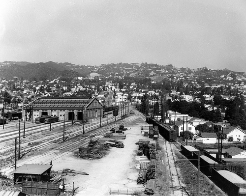 "PE's vast West Hollywood Shops in about 1946. A Hollywood car and PCC can be seen in front of doors #2 and #3. The shops did ""running repairs"" for Western District cars for decades. With the September 1954 abandonment of the Hollywood Bouleard Line , the shops were no longer accessible  by Glendale -Burbank Line cars. By the end of 1954, the Glendale-Burbank Line was an ""electrified island"" in a sea of asphalt, under siege by a pro bus / anti-rail MCL management. Ralph Cantos Collection."